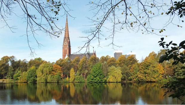 Hamburg - St. Gertrud Kirche (Uhlenhorst-Hohenfelde), rechts die Mundsburg-Hochhäuser